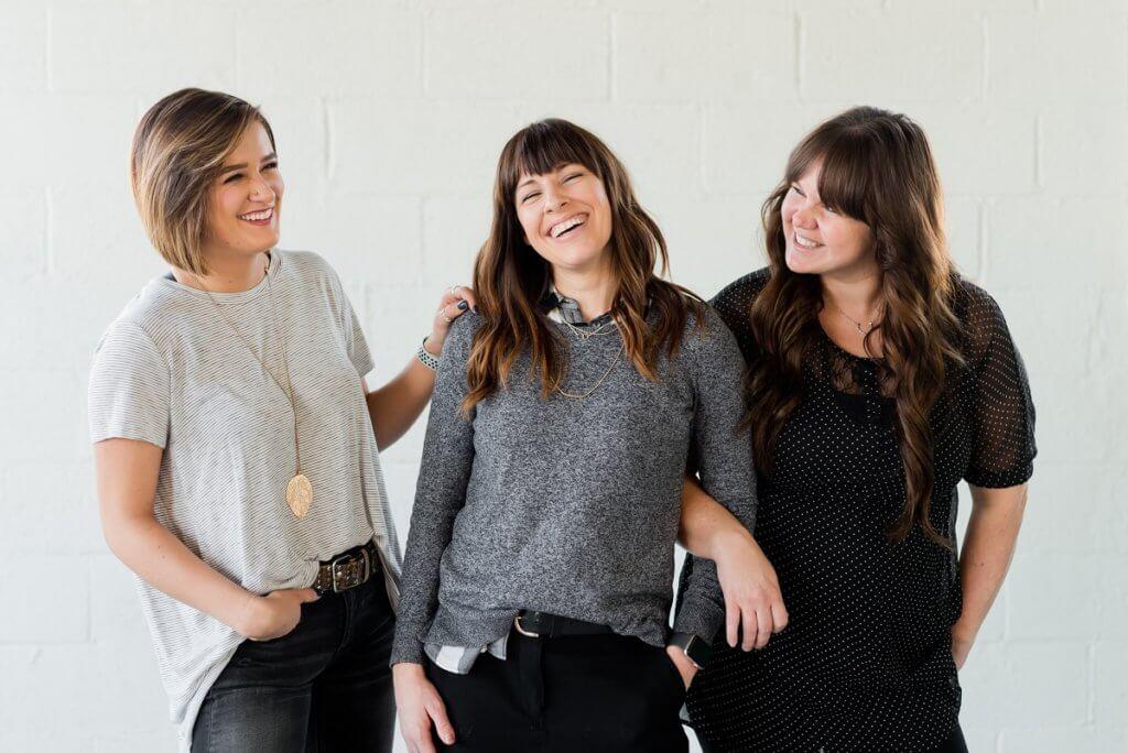 three white women standing and smiling