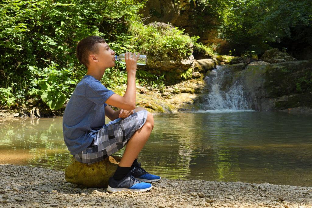 boy drinking water by lake