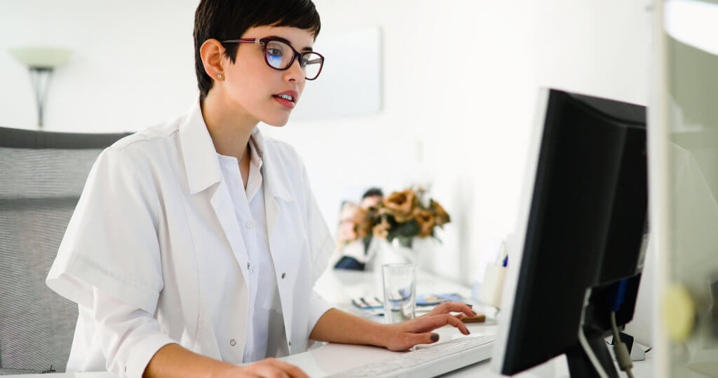 female doctor sitting at a computer desk