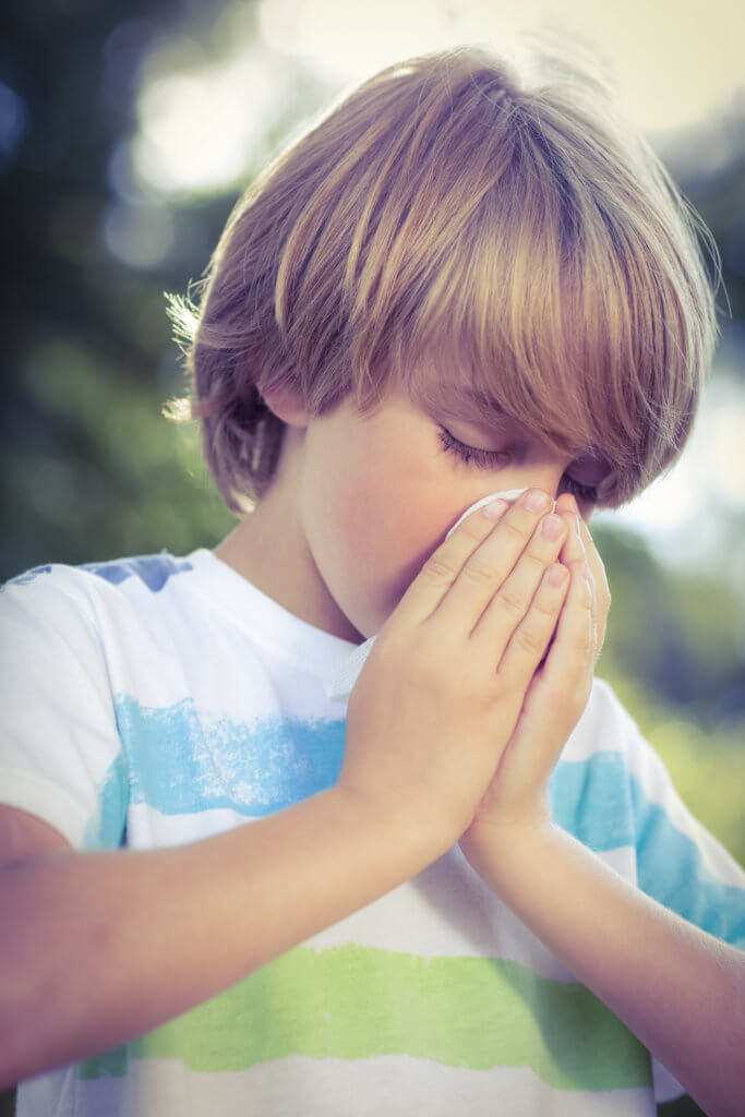 young blonde boy blowing his nose in tissue