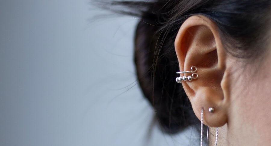 multiple ear piercings on grey background