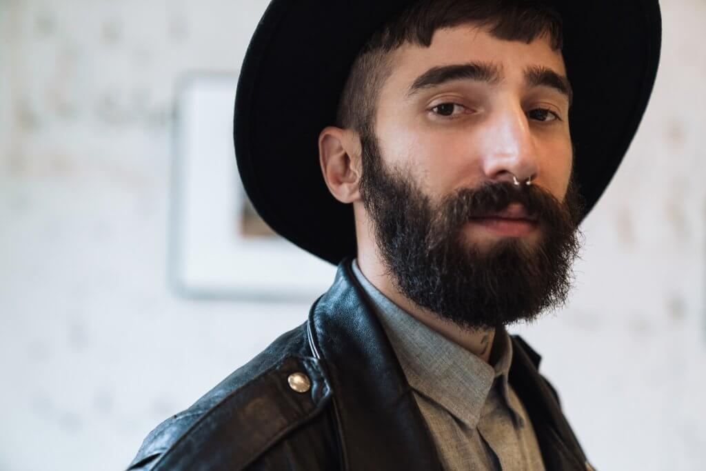 bearded man wearing a hat and nose piercing