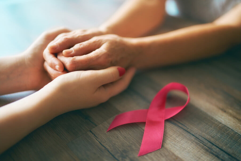 two women holding hands with pink ribbon