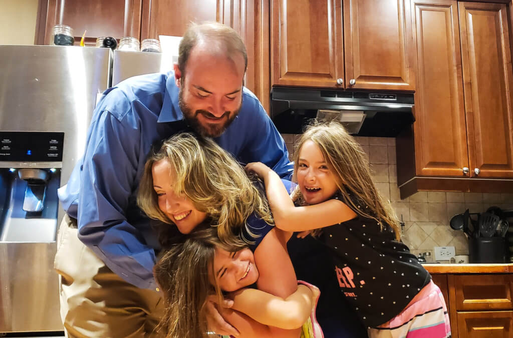 mom, dad and two little girls hugging in the kitchen