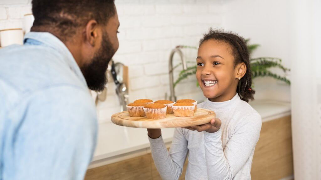 young girl showing her dad a plate of muffins