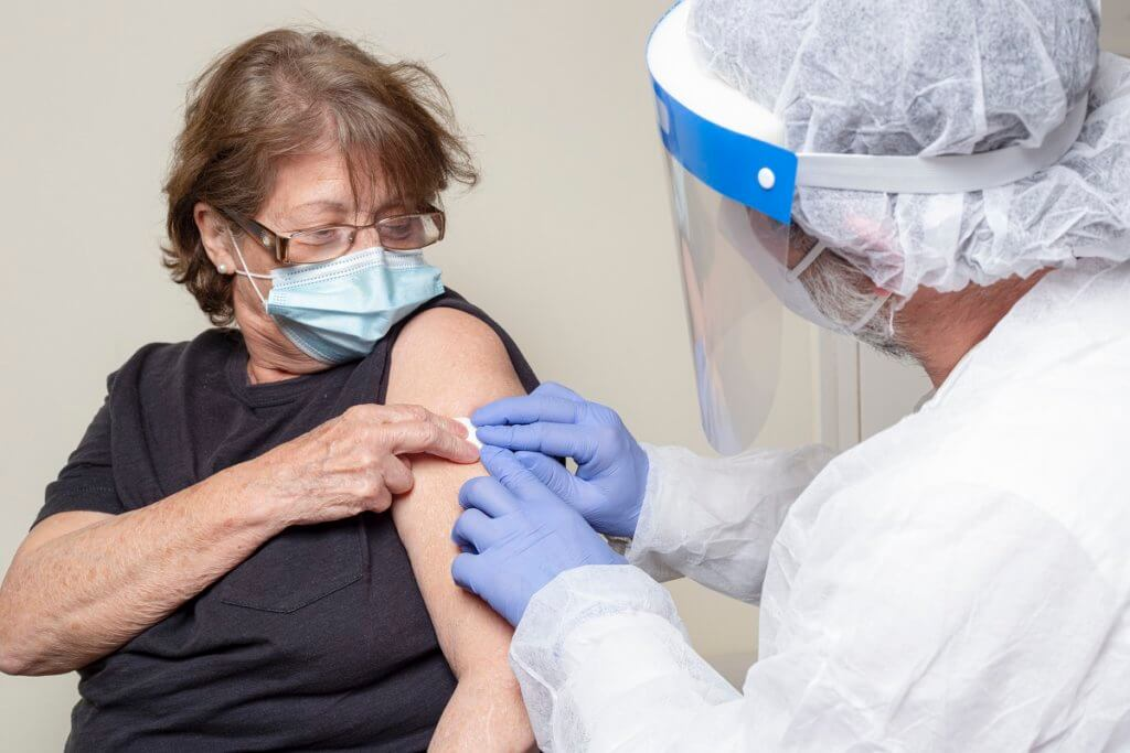 an older woman receiving a vaccine