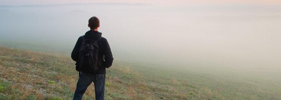 Man standing in fog meadow.