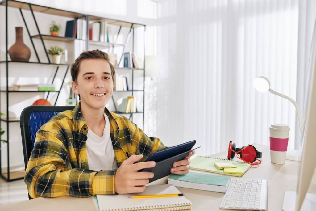 Portrait of cheerful teenage boy sitting at his desk with digital tablet in hands and smiling at camera
