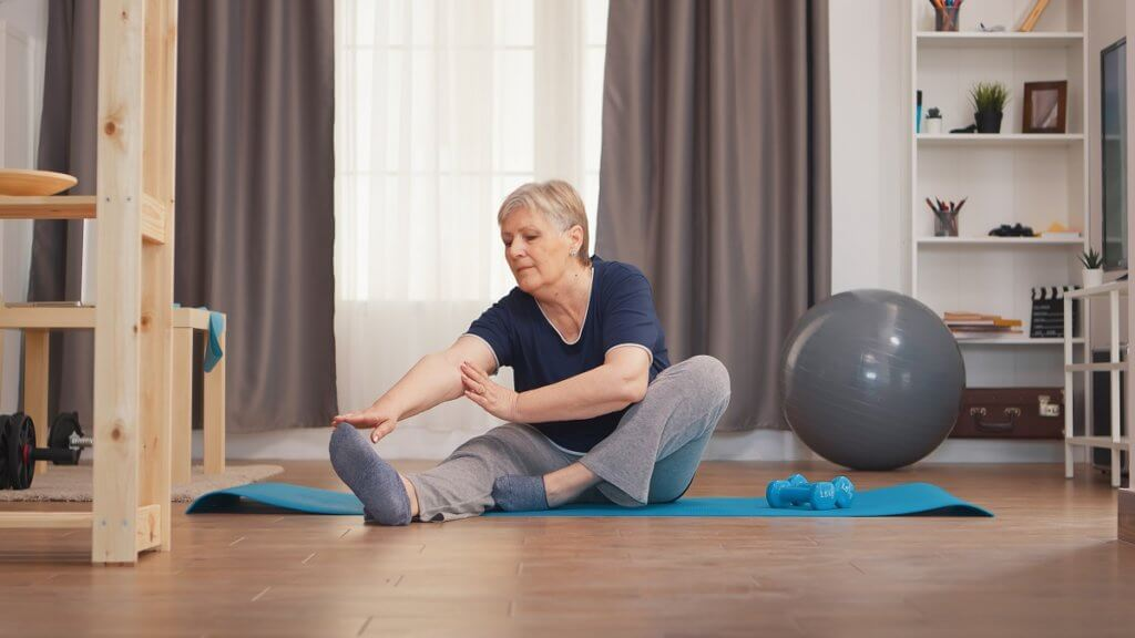 woman stretching legs sitting on yoga mat in living room.