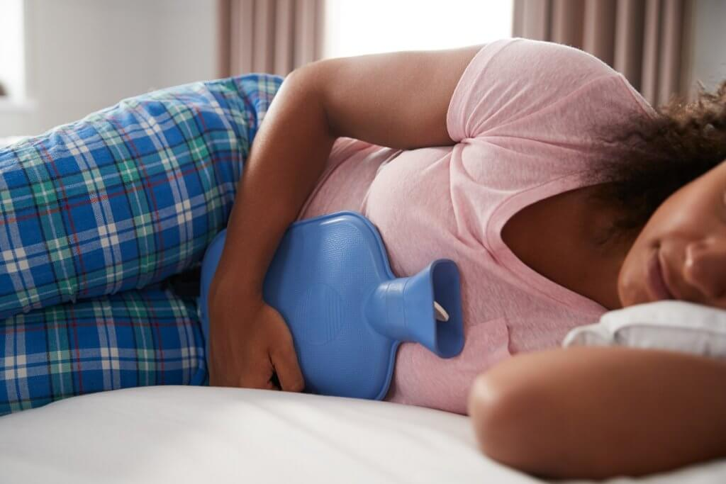 woman laying on bed with hot water bottle