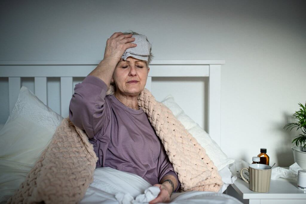 Sick senior woman with headache in bed at home