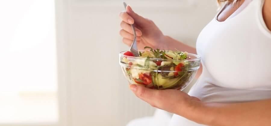 Pregnant woman eating fresh healthy salad
