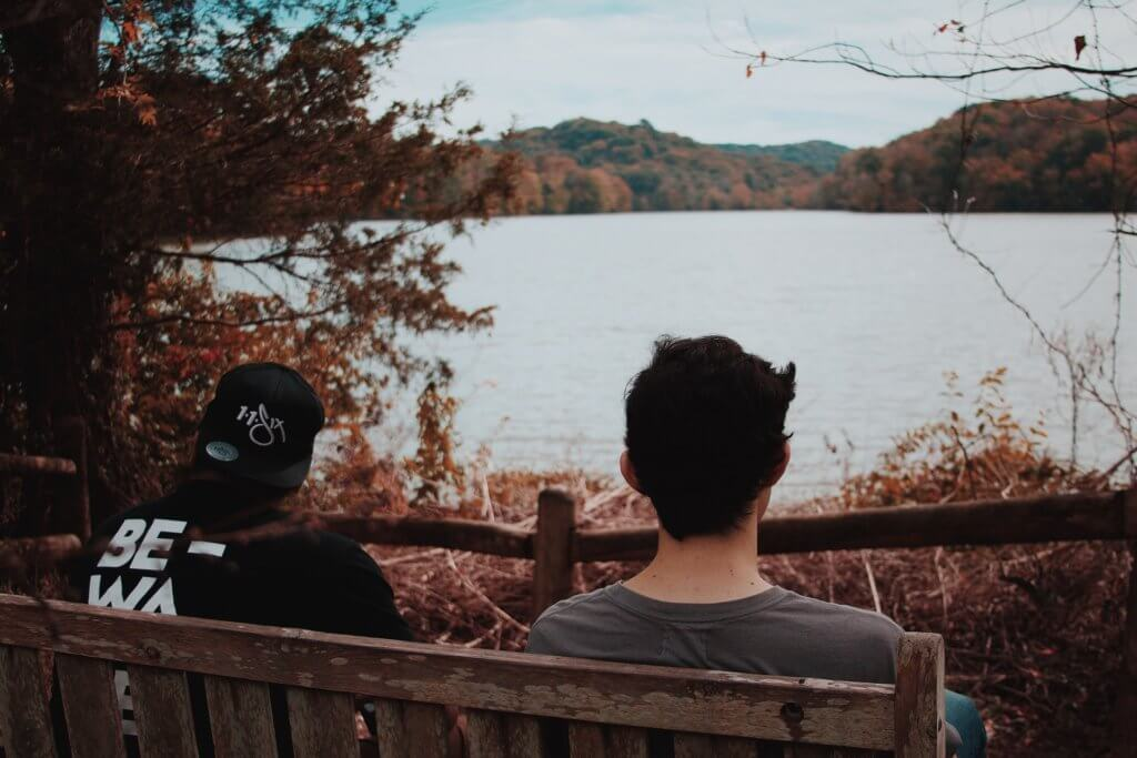 two men sitting on a bench
