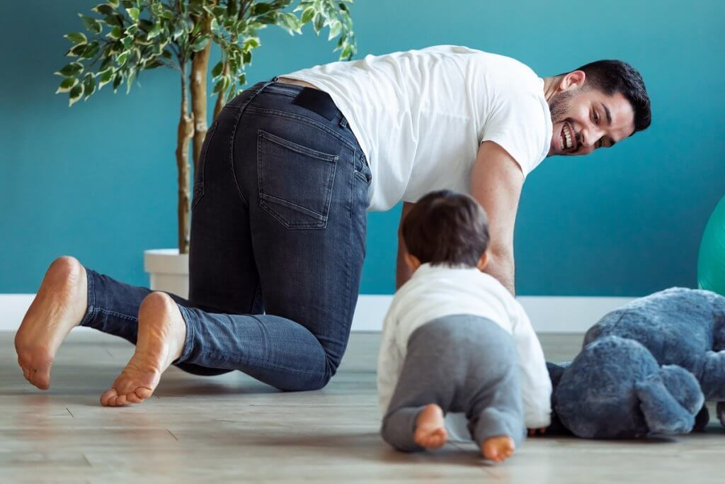 Shot of smiling young father has fun with little baby while are crawling on the floor together at home.